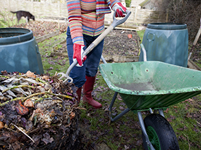 Person building compost in her backyard.